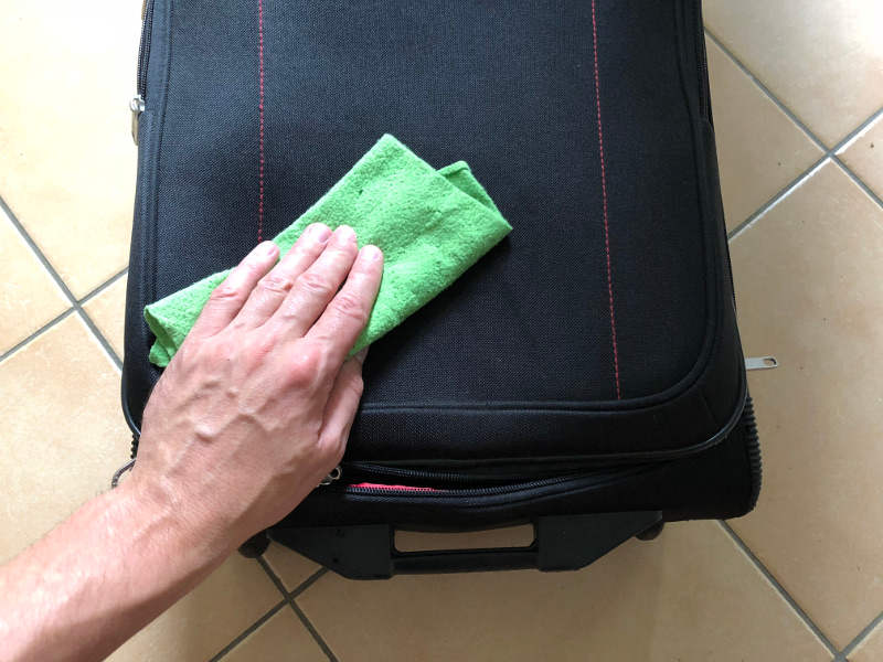 Koffer mit feuchtem Tuch abwischen