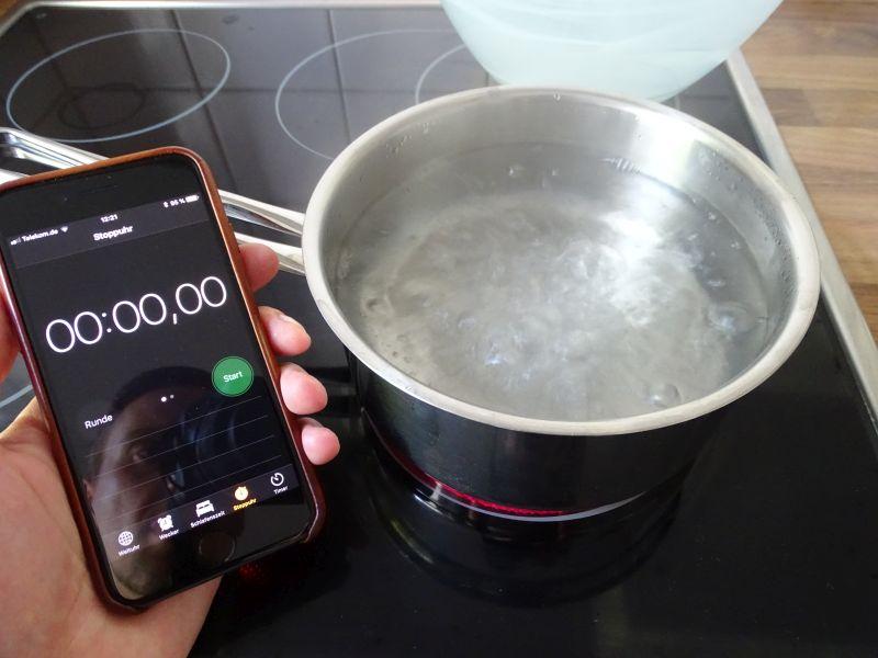 Kochendes Wasser und Timer Eieruhr stellen